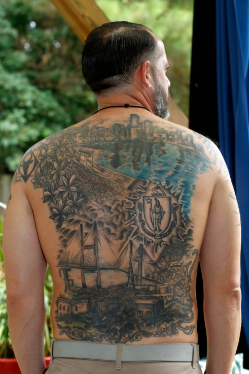 Mike Proto, 37, an elementary school teacher from Peabody, Massachusetts, shows off his full back-piece tattoo in his backyard. Proto got the tattoo to signify his life in Boston and the transition to family-life in Savannah, Georgia.