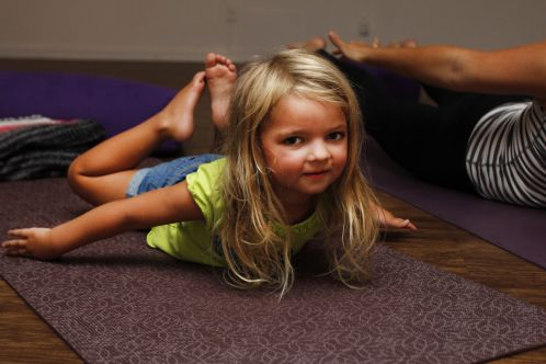 Libby Elze, 4, tries to get everything except her stomach off of the floor at children's yoga at Infuse Yoga on St. Simons Island.
