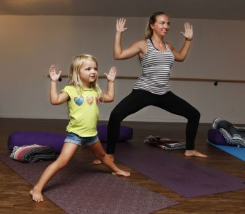 Above Libby Elze, 4, left, practices a few different yoga poses with her mother Ashlyn Elze, while Jaden Brooker, 5, concentrates on stretches with his uncle, Dustin Brooker, at a children's yoga session on Tuesday at Infuse Yoga on St. Simons Island