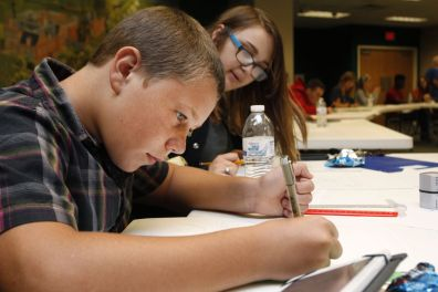 Skyler Stone, left, creates a comic about a dinosaur who thinks he can survive anything and quickly finds out that he can't. Stone was part of the comic class in this year's Amazing Authors Club at the library.