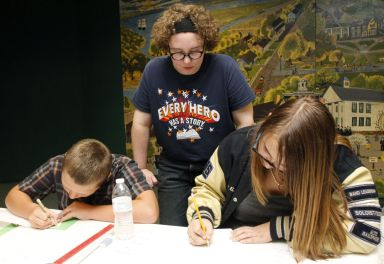 Ingram Jinkins, middle, teaches Skyler Stone, left, and Cheyenne Brundage, right, how to tell their stories through comics in the Amazing Authors Club at the Brunswick-Glynn County Library.