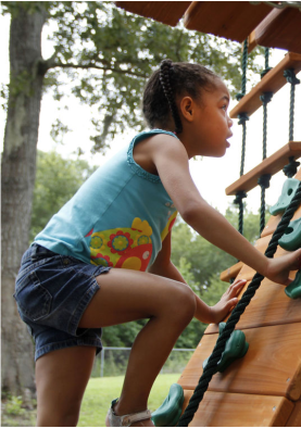 Delilah Mulling, 7, climbs Tuesday on a playset in her backyard in Brunswick given to her by the Make-A-Wish Foundation.